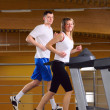 Attractive couple is running on the treadmill — Stock Photo #10862536