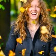 Happy woman is throwing dry autumn leaves in park — Stock Photo