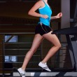 Stock Photo: Beautiful womis running on treadmill