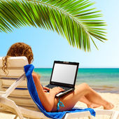 Surfing on the beach. Laptop display is cut with clipping path — Stockfoto