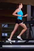 Beautiful woman is running on the treadmill — Stock Photo