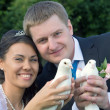 Portrait of the newlyweds in the hands of the white pigeons — Stock Photo