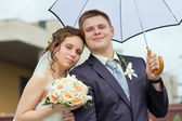 Bride and groom under a white umbrella — Stock Photo