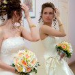 Stock Photo: The bride looks in the mirror