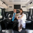 The bride and groom in limousine — Stock Photo
