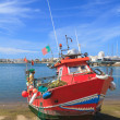 Red painted fishing motorboat in Algarve, Portugal - Stock Photo