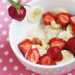Oatmeal Porridge (cereal) on milk with banans, nuts and strawberries - Stock Photo