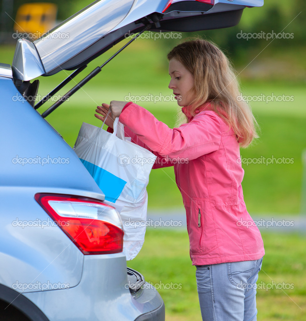 Young woman putting bag in car after shopping. — Stok fotoğraf #10841946