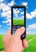 Cell phone in man's hand in a landscape, vertically. — Stock Photo