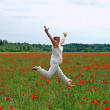 Happy female jumps on poppy field — Stock Photo