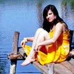 Beautiful brunette sits on a bridge — Stock Photo #11942372