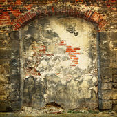 Collapsing stone wall of an old house with brick masonry — Stockfoto