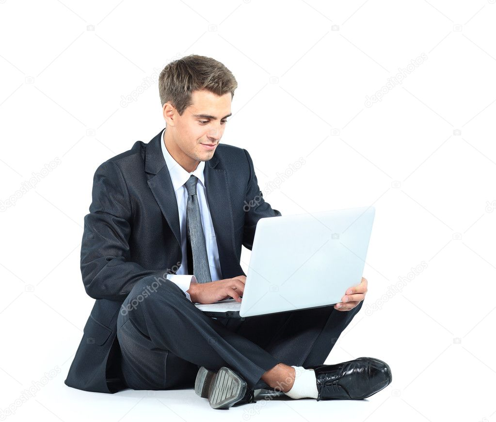 Isolated seated young businessman using a laptop — Zdjęcie stockowe #11041943