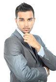 Portrait eines eleganten jungen mannes stehend mit hände gefaltet auf weißem hintergrund — Stockfoto