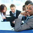 Portrait of smiling African American business man with executives working in background — Stock Photo #11832012