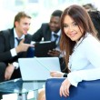 Closeup of a pretty young businesswoman smiling in a meeting with her colleagues in background — Stock Photo #11832020