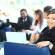 Closeup of a pretty young businesswoman smiling in a meeting with her colleagues in background — Stock Photo