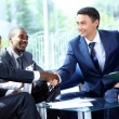 Two business man shaking hands with his team in office — Stock Photo #11832042