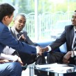 Two business man shaking hands with his team in office — Stock Photo #11832060