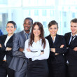 Stock Photo: Happy young business woman with her team in background