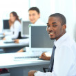 Portrait of a happy African American entrepreneur displaying computer laptop in office — Stock Photo #11832340