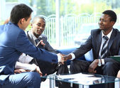 Two business man shaking hands with his team in office — Stock Photo