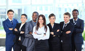 Happy young business woman with her team in background — Stock Photo