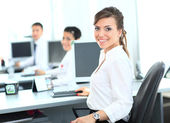 Happy young businesswoman looking behind and her colleagues working at office — Stock Photo