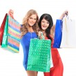 Group of two happy young adult women out of shopping with colored bags — Stock Photo