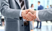 Handshake in front of business — Stockfoto