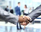 Handshake in front of business — Stock Photo