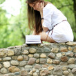 Oung woman in summer, green park reading book — Stock Photo