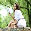 Oung woman in summer, green park reading book - Stock Photo
