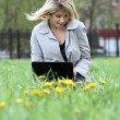 Young blond having fun with laptop outdoors — Stock Photo