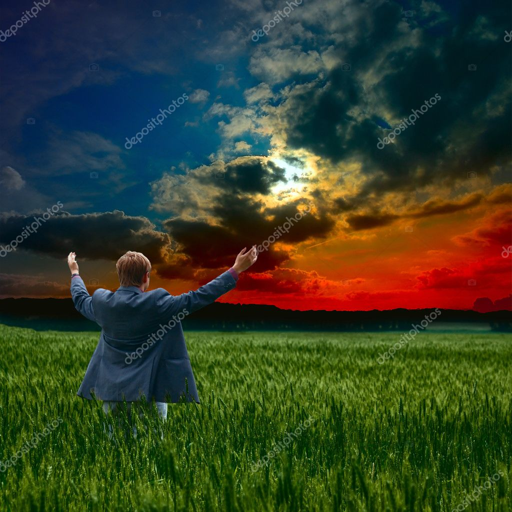 Praying man silhouette on sunset background — Stock Photo #11900418