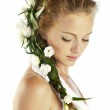 Beautiful young woman with fresh spring flowers in her hair — Stock Photo