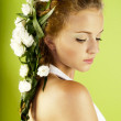 Beautiful young woman with fresh spring flowers in her hair — Stock Photo #11121207