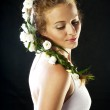 Beautiful young woman with fresh spring flowers in her hair — Stock Photo #11121215