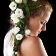 Beautiful young woman with fresh spring flowers in her hair - 