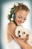 Vacker flicka med hörlurar hålla en hund — Stockfoto