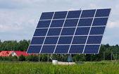 панели солнечных батарей станции между деревьями и луг — Стоковое фото
