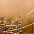 Firemen at work putting out a house fire — Stock Photo