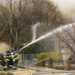 Firemen at work putting out a house fire — Stockfoto