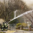 Firemen at work putting out a house fire — Stock Photo #11297763