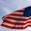 Stock Photo: American flag against blue sky — Stock Photo