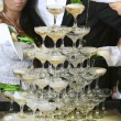Pouring champagne into a glass on a wedding celebration — Stock Photo