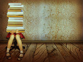 Girl with books sitting on wood floor in old dark room.Grunge ba — Stok fotoğraf