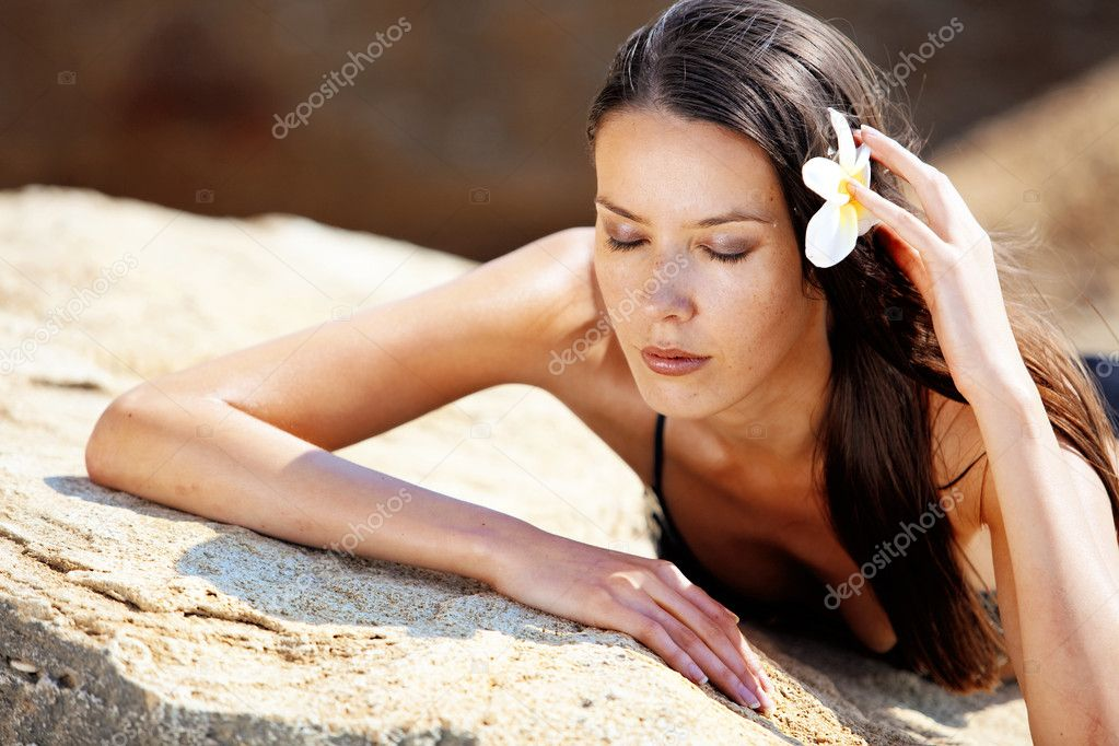 Closeup portrait of beautiful young woman with golden tan resting at beach in summer  Stock Photo #11442423