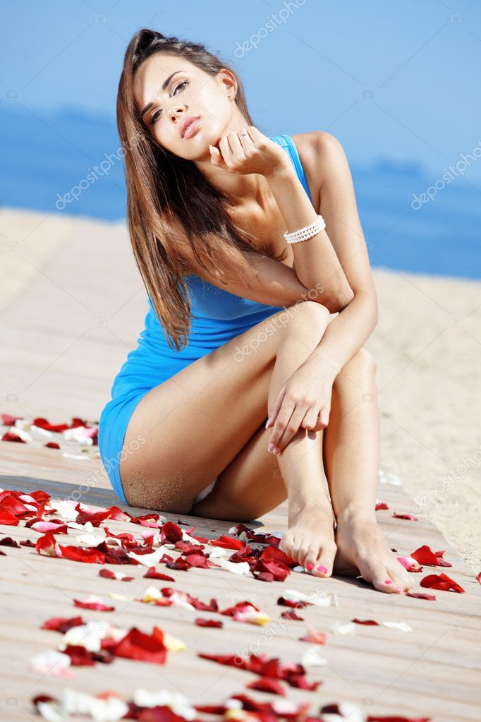 Portrait of young beautiful woman resting at the beach among rose petals — Stock Photo #11891460