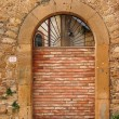 Stock Photo: Old arched door blocked by brick wall